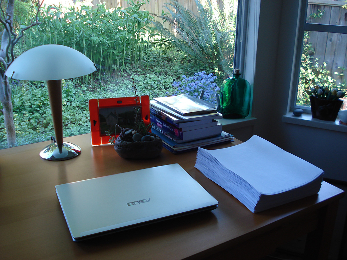 The first draft of The Broken Places sitting on a desk, with a lamp and a large window behind