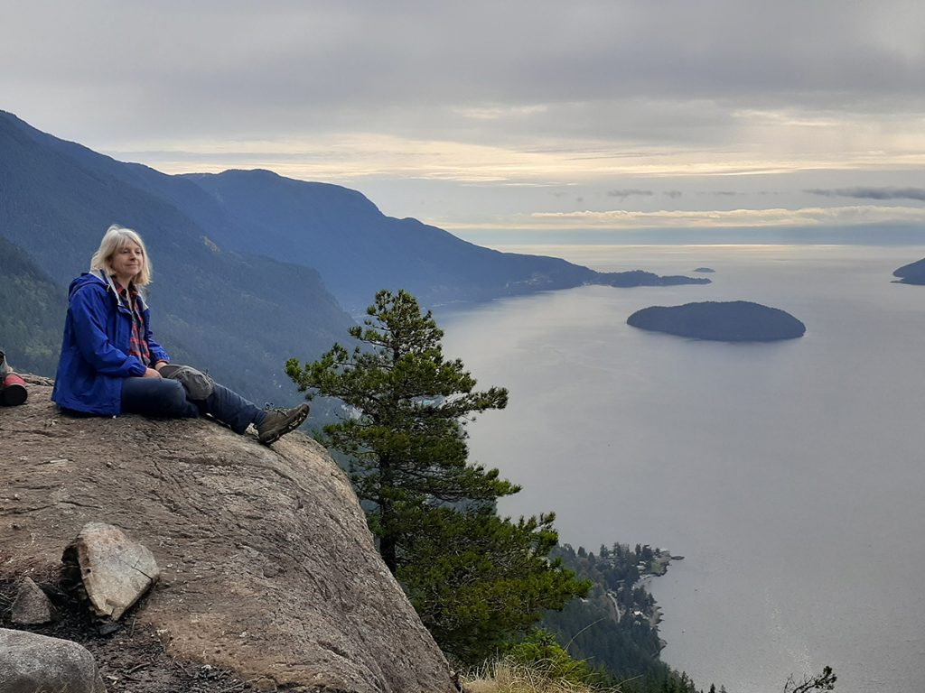 Frances Peck sits at a viewpoint overlooking the water