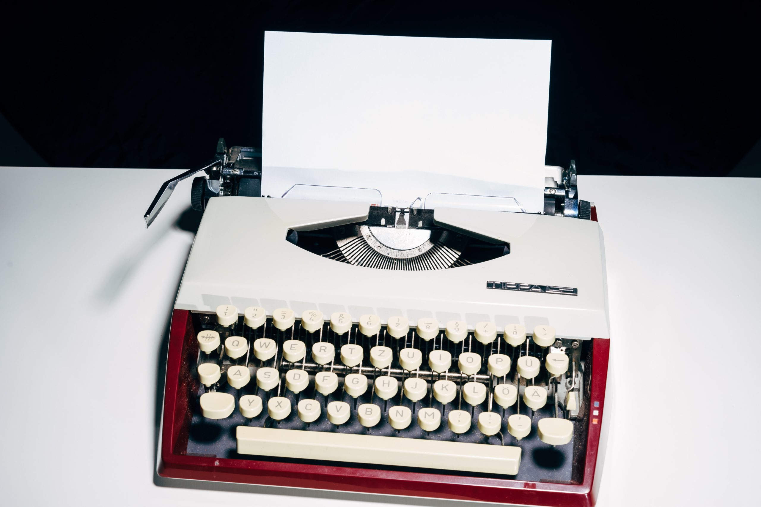A red and white typewriter with a piece of paper coming out of the top